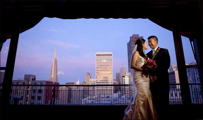 High ceilings of University Club frame bride and groom with bouquet before San Francisco skyline