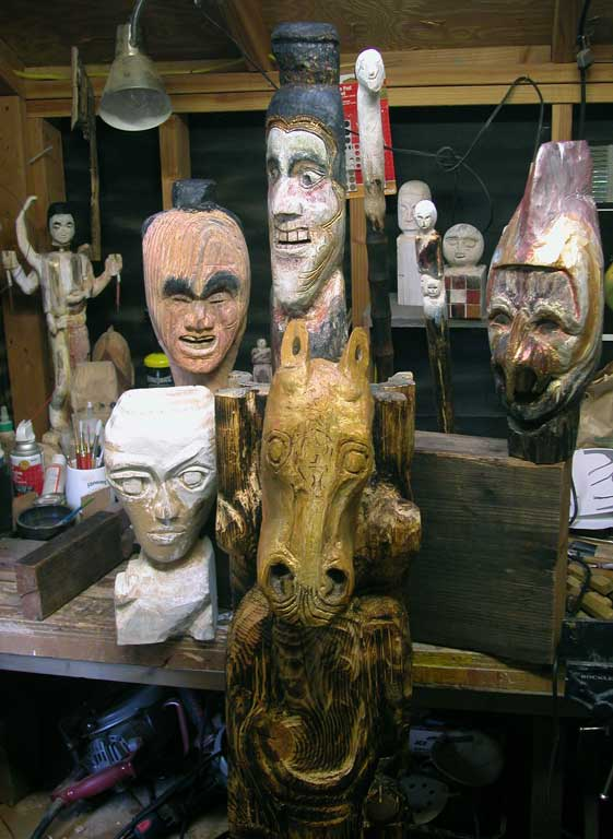 wood sculpture masks and heads pose for photograph
