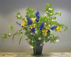 large arrangement of lilies, delphiniums, Cecile Bruner Climbing