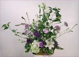 Sympathy flower arrangement of lisianthus liliesin basket
