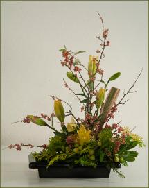 branch ikebana with colorful lilies, harakeke Asiatic style