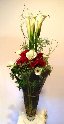 cala liliesred roses in tall arrangement front view
